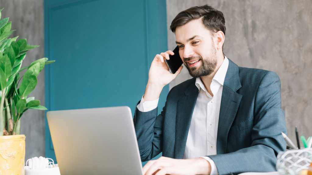 business man talking on cloud-based phone system while looking at laptop