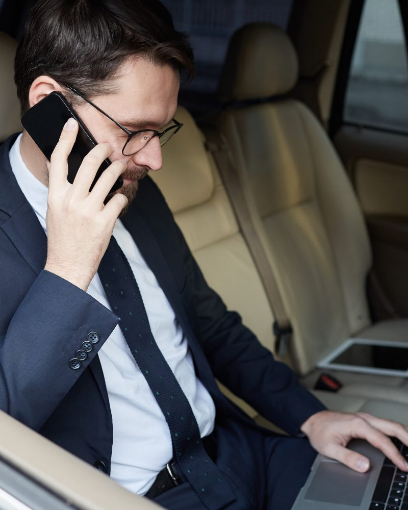 Man sitting in car talking on his business communications cell phone